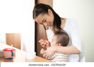 Mother feeding baby food to her baby