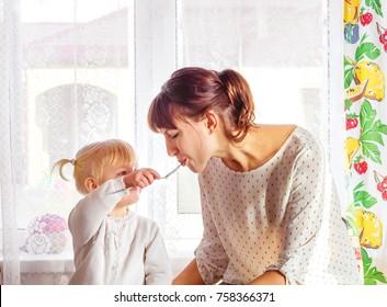 Mother feeding baby food. Young woman feeding kid daughter yogurt on kitchen.