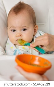 Mother feeding baby girl with mashed avocado and green vegetable in an orange plastic bowl, food on a plastic spoon; concept of family life, healthy eating and baby nutrition