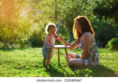 Mother feeding baby girl with watermelon in the garden. Summer, People, Nature, Outdoors, Family life