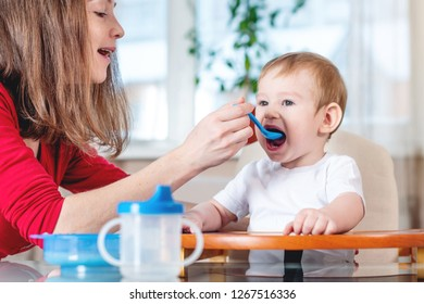 Mother feeding the baby holding out her hand with a spoon of porridge in the kitchen. Emotions of a child while eating healthy food.