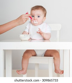 Mother feeding baby with a spoon. Spoon-feed.