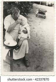 mother feeding a baby with a spoon. USSR 1950s 20 century