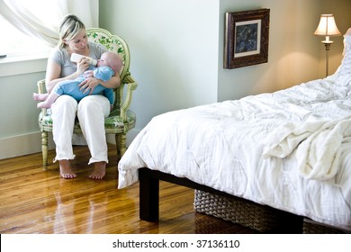 Mother feeding bottle to seven month old baby in bedroom