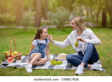 Mother Feeding Daughter Giving Her Grapes Having Family Picnic In Park Outside. Summer Weekend Leisure.
