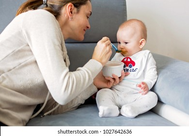Mother, feeding her baby boy with mashed pumpking for the first time