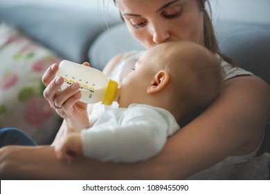 Mother, feeding her baby boy from bottle, comfortably sitting on the couch at home