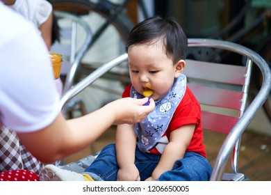 Mother feeding her baby boy with a spoon