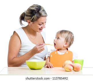 mother feeding her baby girl by spoon