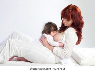 Mother feeding her baby. Half lying