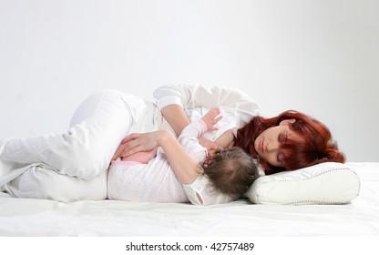 Mother feeding her baby. Side lying