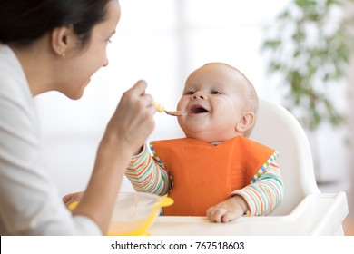 Mother feeding her baby son with spoon. Mother giving healthy food to her adorable child at home