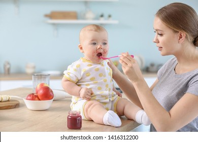 Mother feeding her little baby in kitchen at home