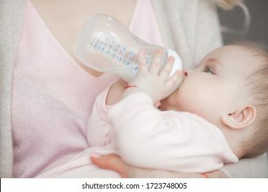 Mother feeding her little baby. Child eating formula.