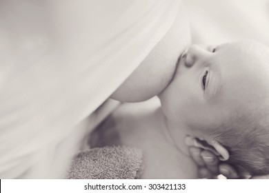 mother is feeding her newborn with breast