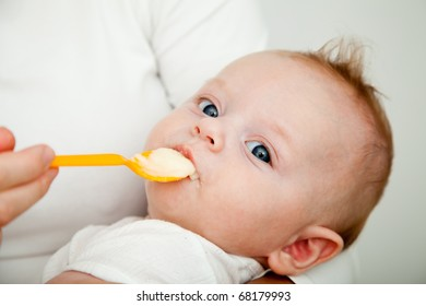 Mother feeding her picker son with spoon, but he refusing to eat
