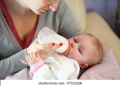 Mother feeding infant girl with a milk bottle