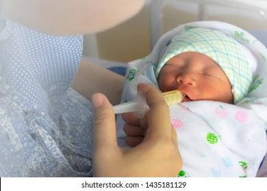 Mother feeding newborn baby milk with syringe