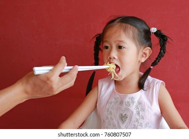 Mother feeding noodle for her daughter on high chair against red wall background.