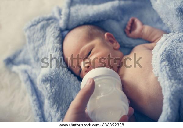 Mother feeding one weeks old newborn baby boy.