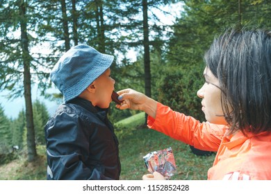mother feeding son with chocolate at forest