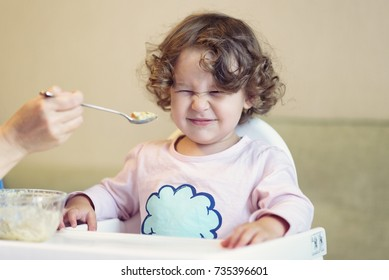 Mother feeds the baby girl with a spoon. The two-year-old child is naughty and refuses to eat. Cute baby grimaces because he does not like the food. Portrait of funny baby with problems.