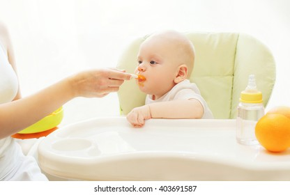 Mother feeds baby spoon sitting for table home