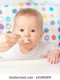 Mother feeds funny baby from a spoon