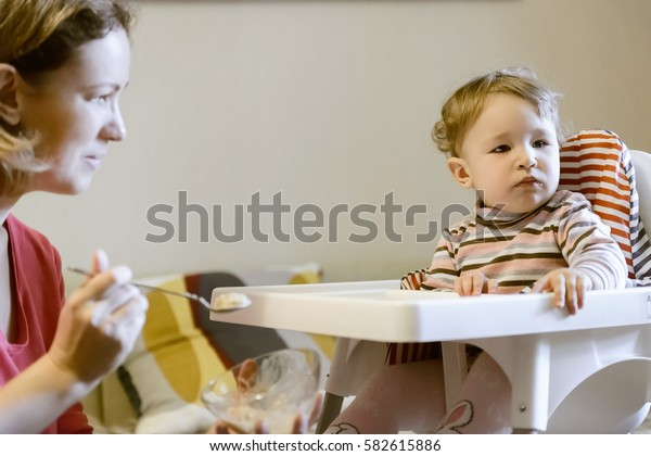 Mother feeds her baby girl with a spoon. The one-year child sits on a high chair and looks aside.