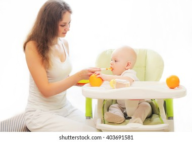 Mother feeds little baby spoon on table at home