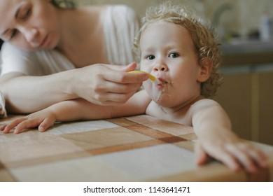 Mother feeds a little girl