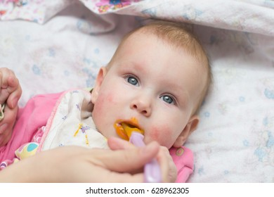 Mother feeds mashed potatoes and porridge with a spoon a beautiful little baby girl, whose mouth is mashed in mashed potatoes or porridge