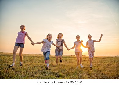 Mother and four kids having fun in the field, holding hands and running towards camera outdoors,  at summer field at sunset. They are wearing casual clothes. Close-up photo.