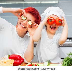 Mother and funny daughter playing in the kitchen with vegetables