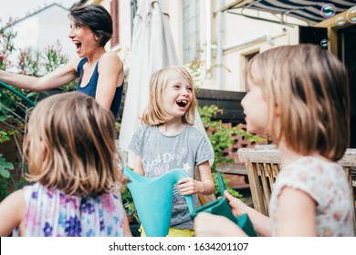 Mother gardening at home with three daughter - green living, ecological, environmentalism concept