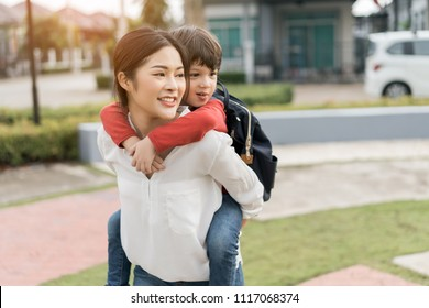 Mother get a son pupil piggyback ride from school after study school going to home with schoolbag family lifestyle.