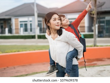 Mother get a son pupil from school after study school back to home with schoolbag family lifestyle.