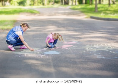 mother and  girl draws with chalk on  pavement
