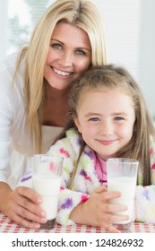 Mother and girl drinking milk while smiling in kitchen