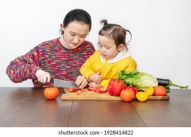 Mutter und Mädchen säubern Gemüse in der Küche auf