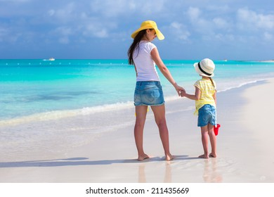 Mother and girl at tropical beach during summer vacation
