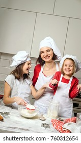 Mother with girls prepare dough for baking in kitchen. Christmas tradition. Cooking concept