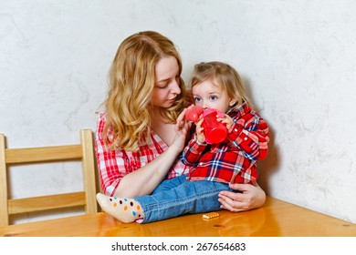 Mother give drink her baby girl by feeding bottle. Sitting in the kitchen. Happy family.