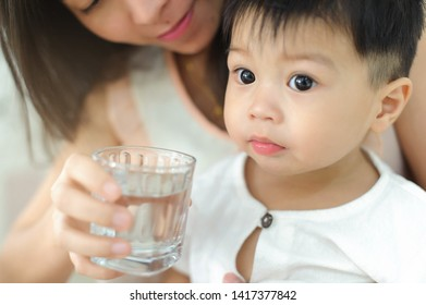 Mother give glass of water for a baby child.