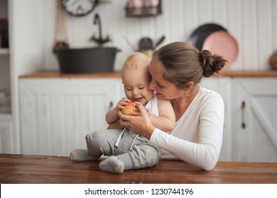 mother gives the baby an apple, mother hugs her son. Real interior, bright kitchen. The concept of healthy eating in the family, healthy teeth and the right food.