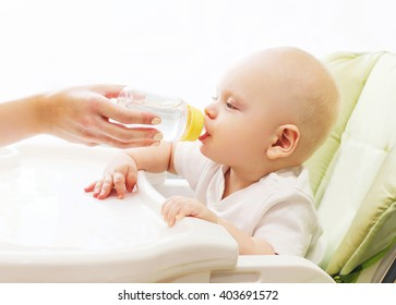 Mother gives baby water of plastic bottle at the table home