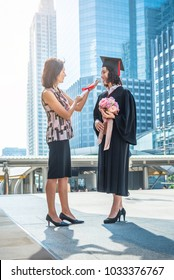 Mother gives bouquet of flower to her daughter for congratulations, whom finish their studies at the university. Parents congratulate the student.