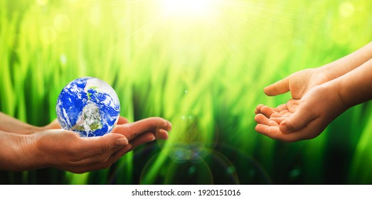 Mother gives the child the planet earth in her hands. Environmental protection for the new generation. Save Earth. World Earth Day. Elements of this image furnished by NASA