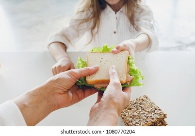 Mother gives daughter sandwich close up. Healthy breakfast