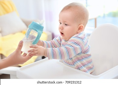 Mother giving baby bottle with water indoors